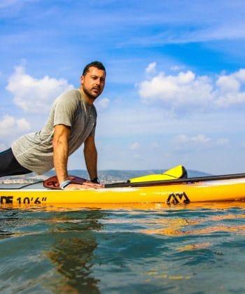 Réalisation d'une posture de yoga à la fin d'un coaching paddle